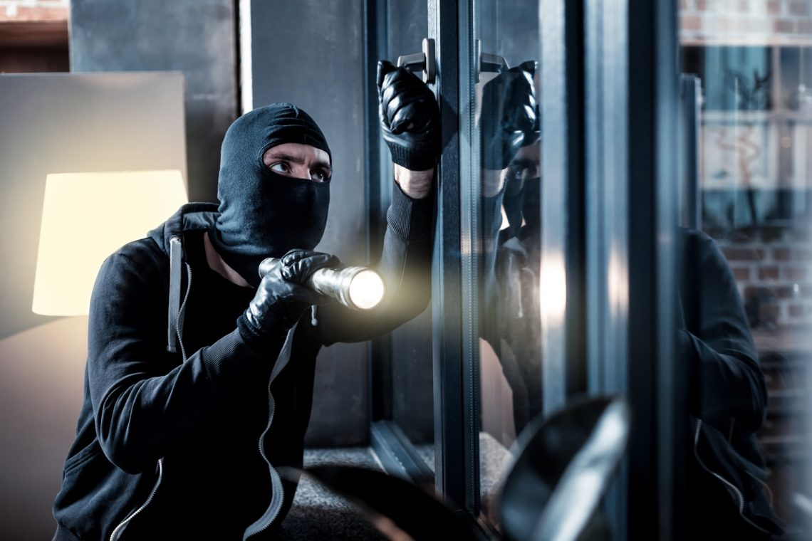 Burglary. Skilful professional masked burglar opening a window and holding a torch and breaking into the house